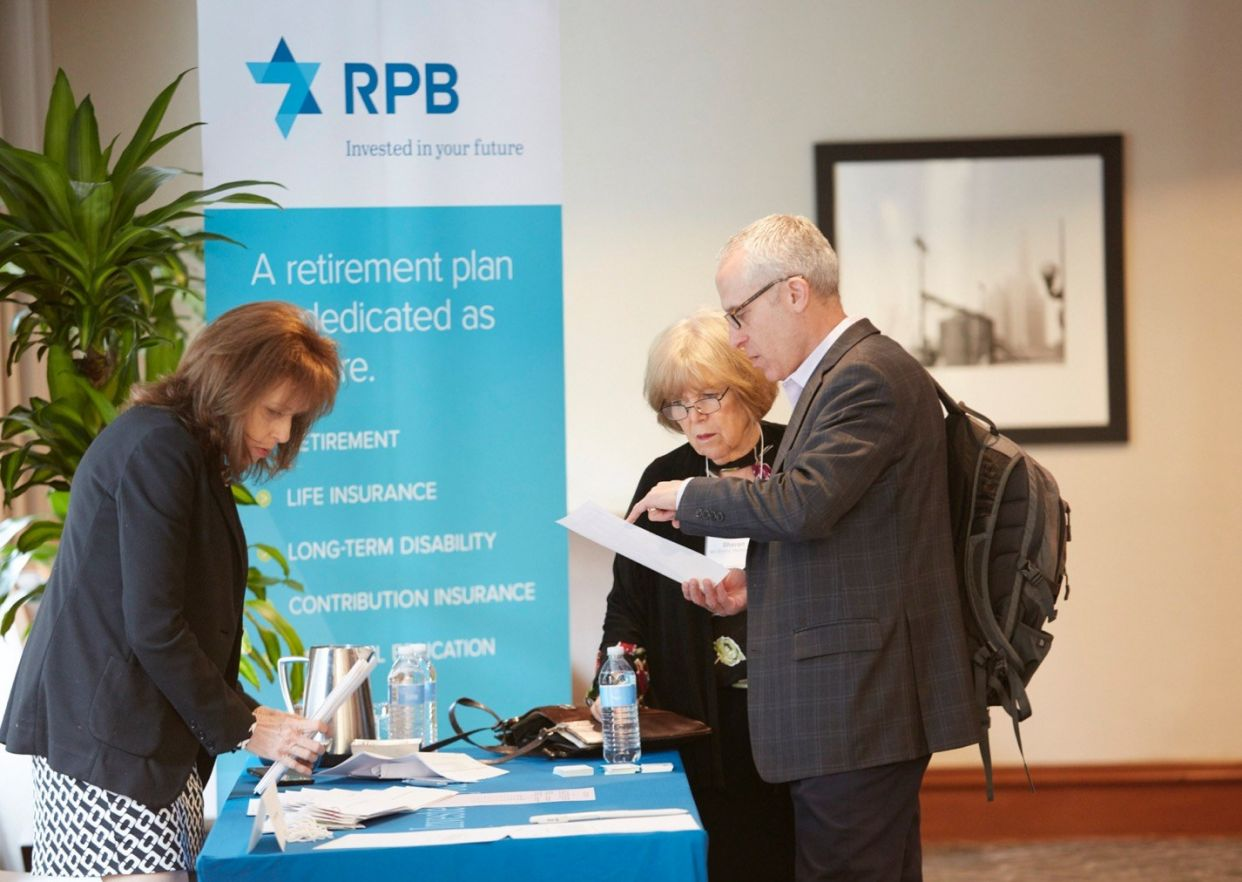 Retired couple talking to a woman at an RPB booth.